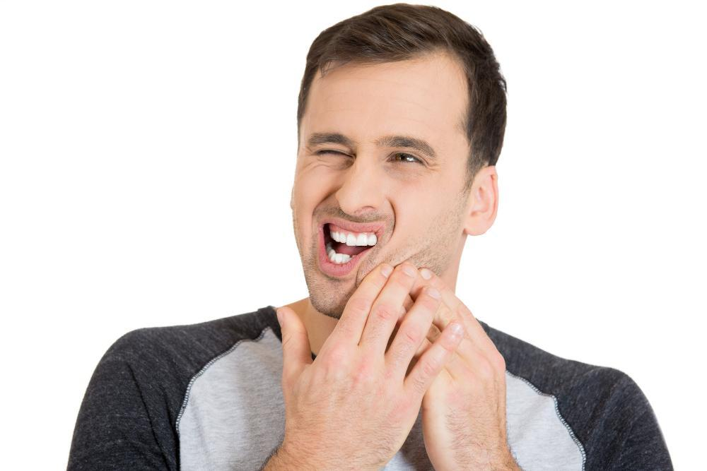 man holding jaw from pain | emergency dentist near me