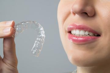 Woman holding invisalign in monroe