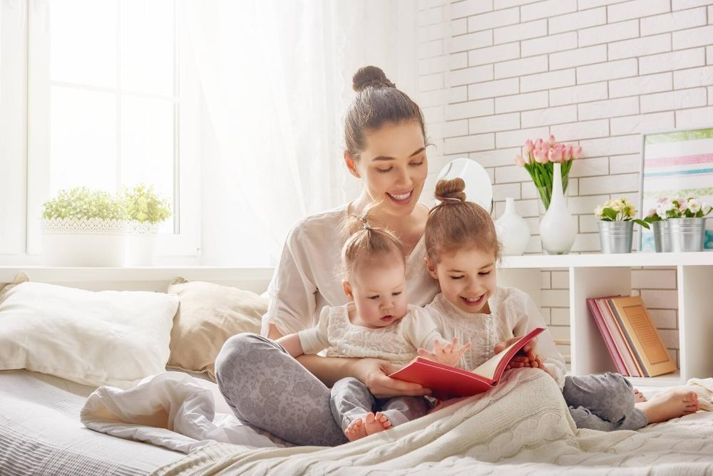 woman reading to her two young children