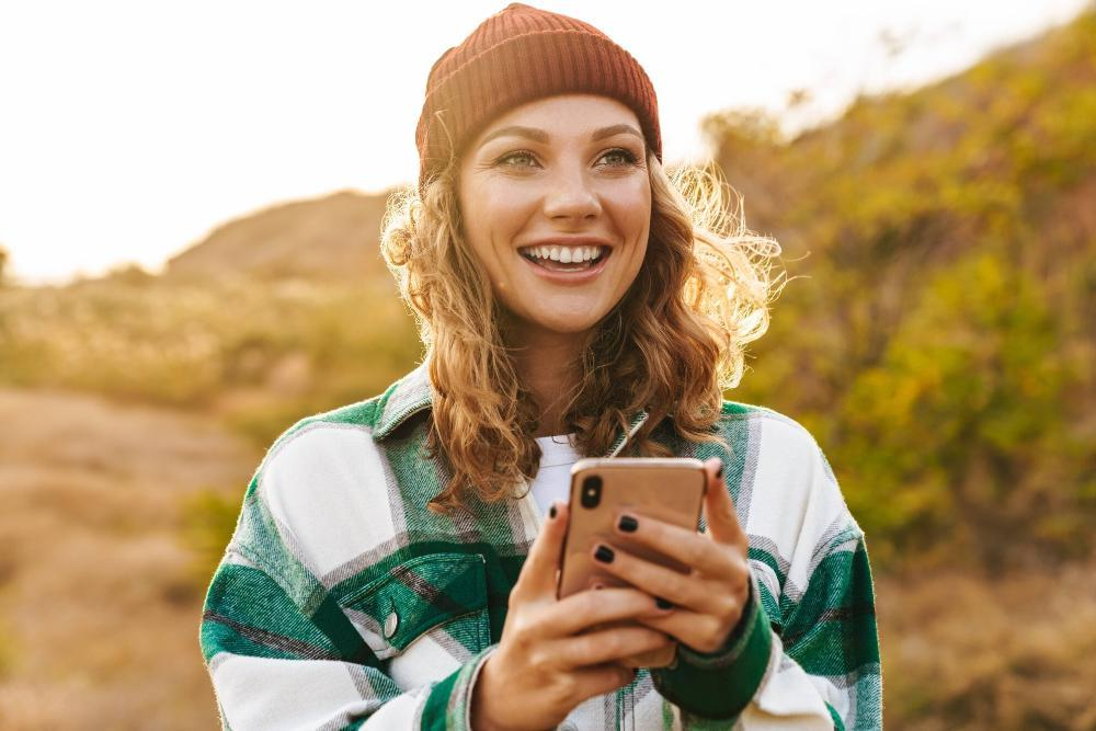 woman holding cell phone smiling